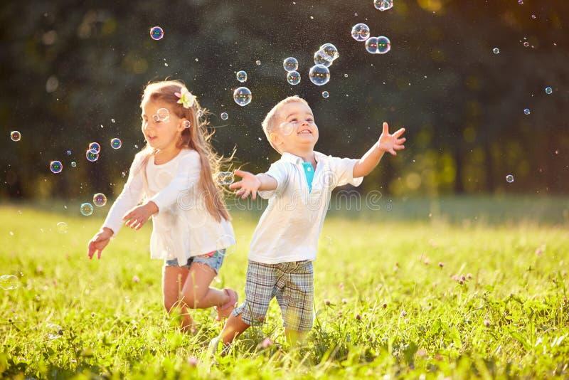 Bolle allegre di inseguimento dei bambini fotografia stock