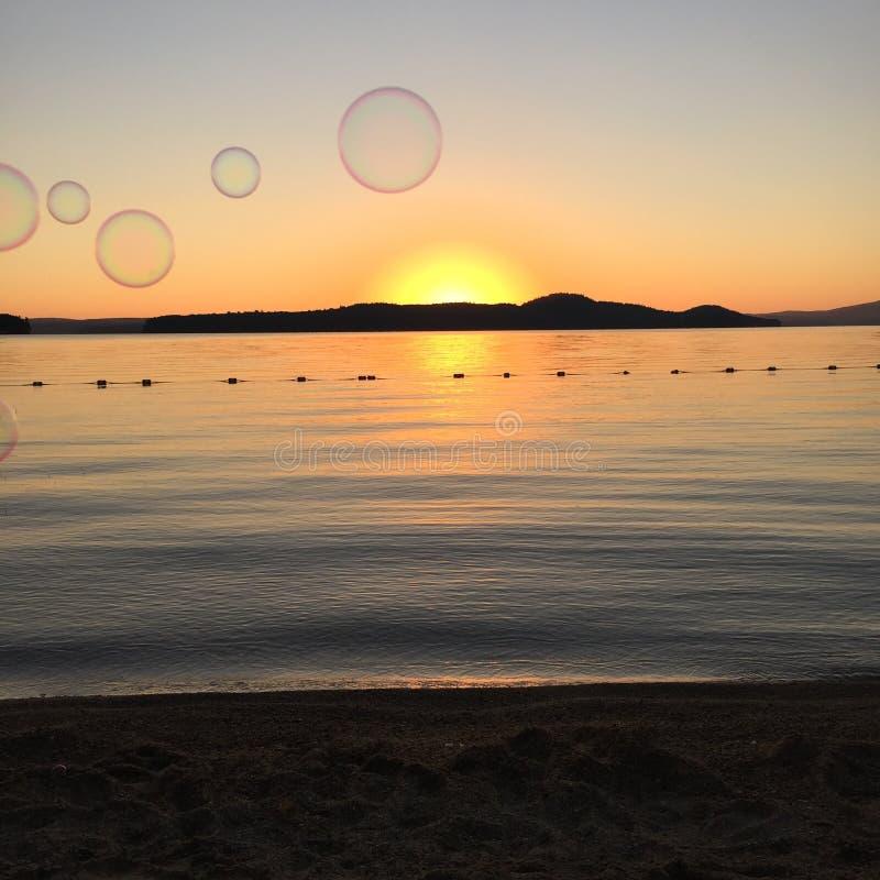 Bolle di salto sul lago al tramonto fotografie stock