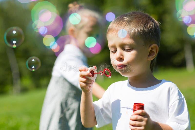 Bolle di sapone felici del colpo dei piccoli bambini immagine stock libera da diritti