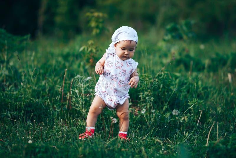 Bolle di sapone di salto della bambina, bambino di un anno del ritratto della molla bello immagini stock
