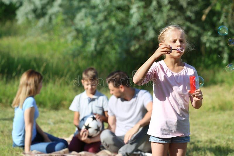 Bolle di sapone di salto della bambina mentre dipendendo dalla sua famiglia in parco fotografia stock libera da diritti