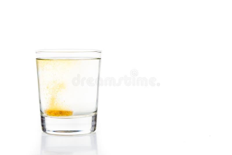 Bolle effervescenti della compressa della vitamina C in bicchiere d'acqua immagini stock libere da diritti