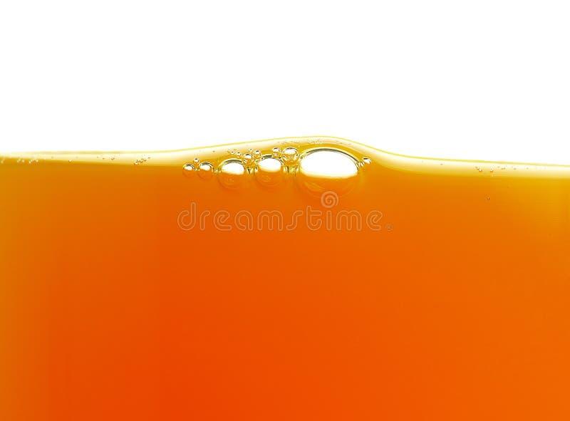 Bolle gialle nel succo d'arancia fotografia stock