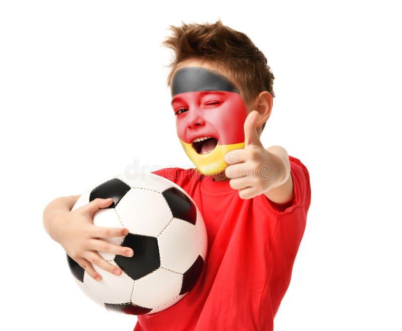 Bollen för fotboll för hållen för fanpojkespelaren som firar lycklig skratta visning, tummar upp tecken med den tyska flaggan på  royaltyfria bilder
