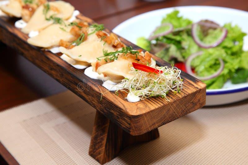 Bollen met aardappels en kaantjes in zure room op een houten raad en een salade stock foto's