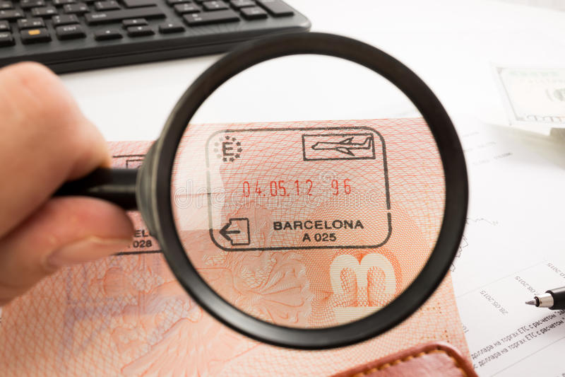 Bolli dell'entrata in pagina del passaporto Lente d'ingrandimento fotografie stock libere da diritti