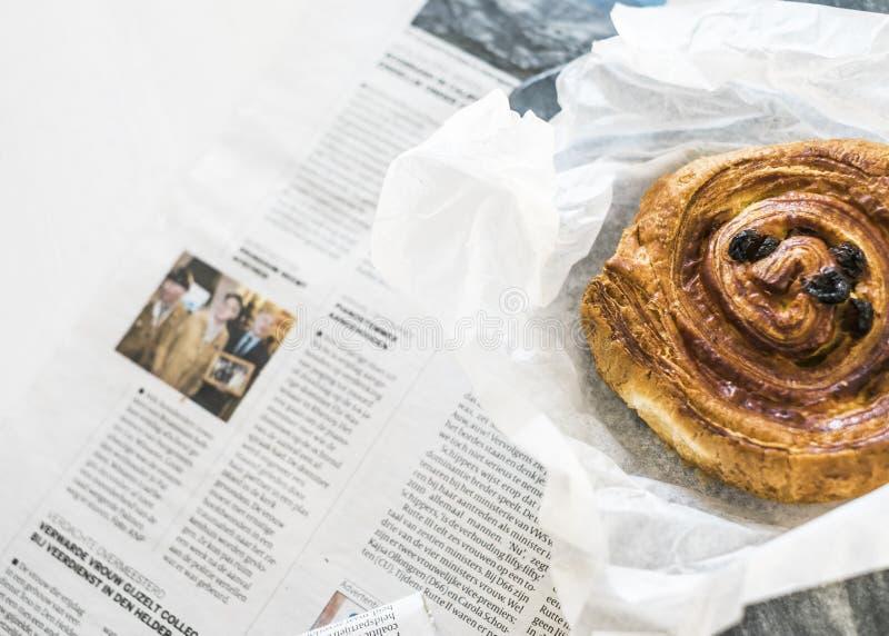 Bollito y periódico daneses del café fotografía de archivo