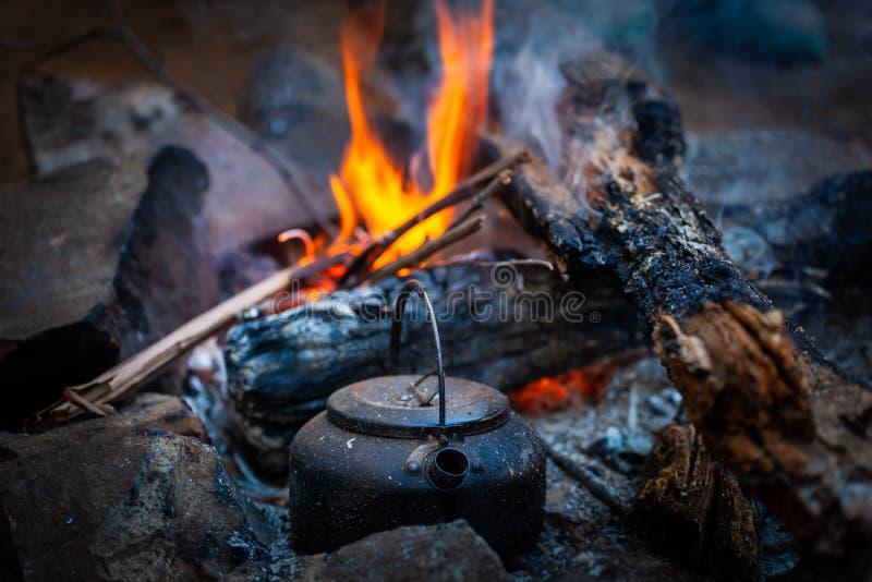 Bollitore del fuoco di accampamento disposto vicino ai carboni brucianti fotografie stock