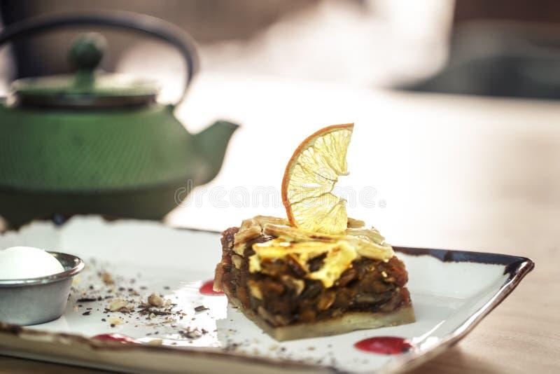 bollitore verde con tè ed il dessert dolce Torta di mele caramellata con il limone ed il gelato freddo immagine stock