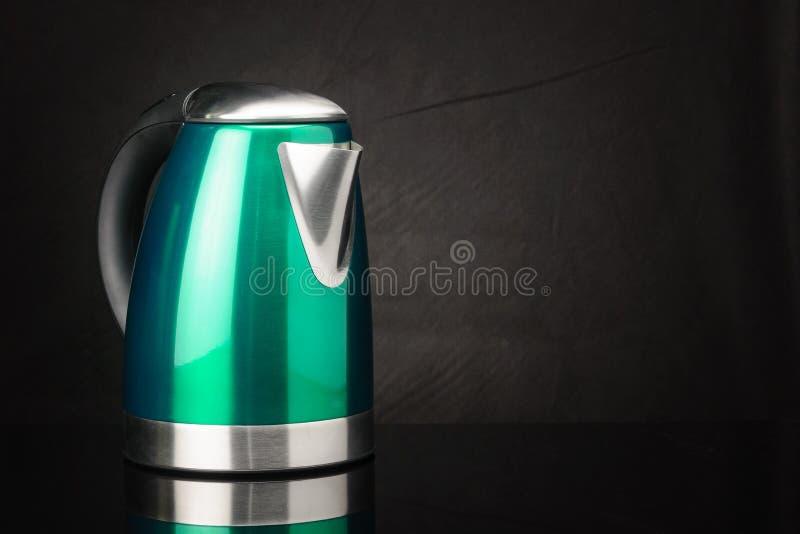 Bollitore verde di acciaio inossidabile sul fondo nero dello specchio con lo spazio della copia fotografia stock