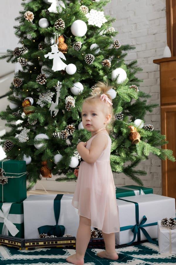 bolljulen isolerade white för mood tre Liten flicka som blir den near julgranen royaltyfri fotografi