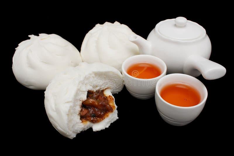 Bollo asado a la parilla chino del cerdo con la tetera y las tazas de té fotografía de archivo