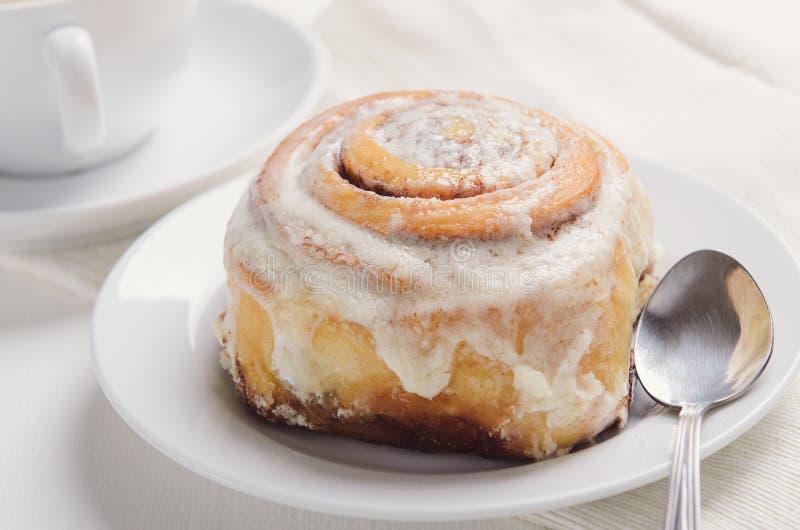 Bollo de canela caliente con la formación de hielo cremosa del azúcar en la placa blanca Desayuno o bocado dulce con una taza de  foto de archivo libre de regalías