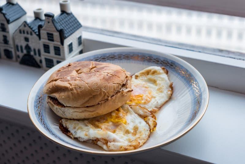 Bollo de hamburguesa chamuscado con los huevos fritos en placa imagenes de archivo