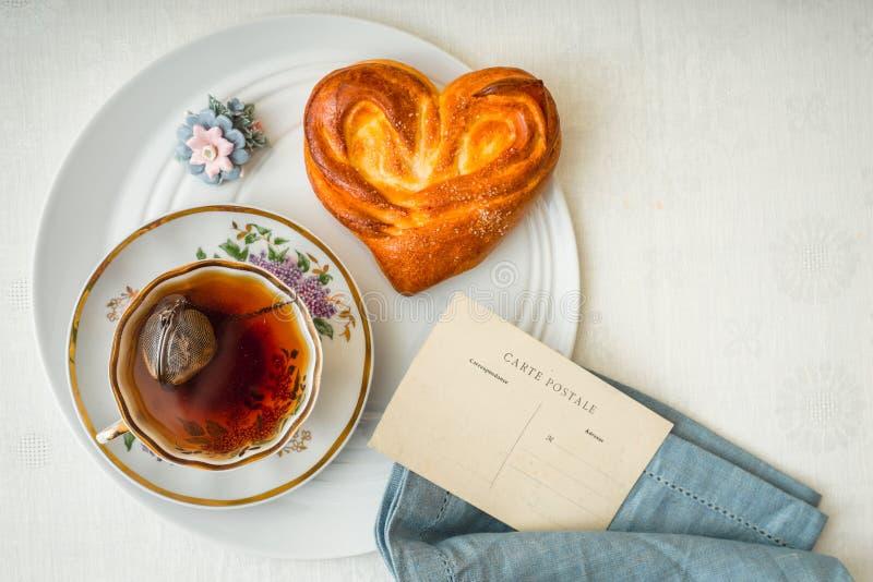 Bollo dulce con la taza de té y la postal en la opinión de sobremesa blanca foto de archivo