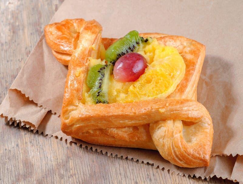 Bollo dulce con las frutas en fondo de madera imagen de archivo