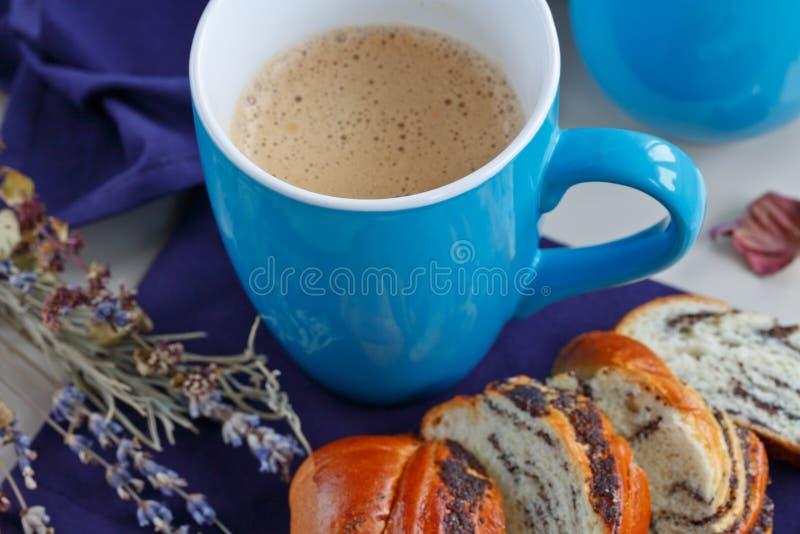 Bollo dulce con las semillas de amapola con una taza de café o de capuchino imagenes de archivo