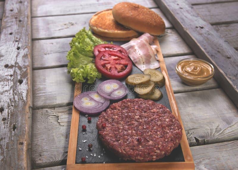 Bollo fresco de los ingredientes de la hamburguesa hecha en casa, pepino salado, empanadas de carne de vaca, tocino foto de archivo libre de regalías