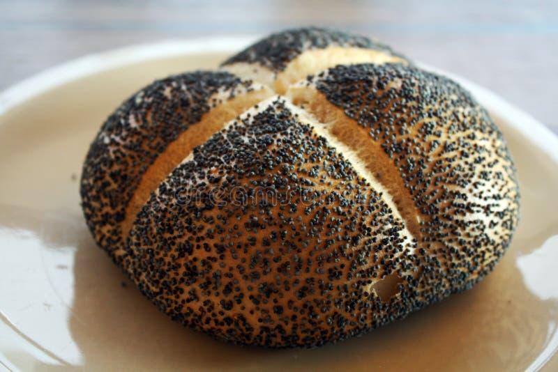 Bollo recientemente condimentado con las semillas de amapola para el desayuno fotografía de archivo