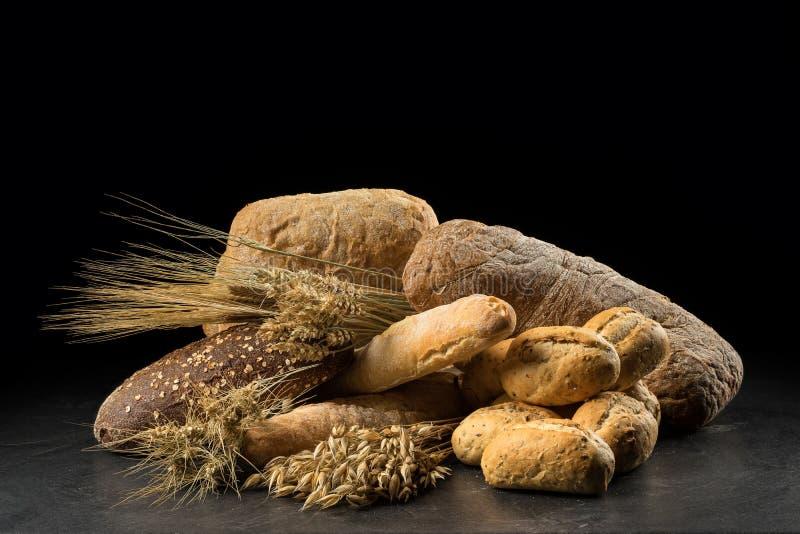 Bollos, baguette, ciabatta y pan en la tabla de madera oscura Rye, cebada, trigo, avena y muchos panes mezclados frescos en vagos foto de archivo