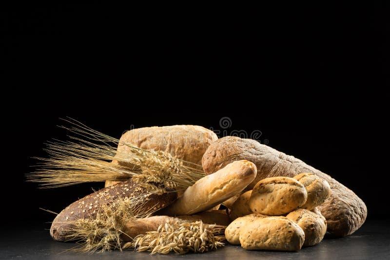 Bollos, baguette, ciabatta y pan en la tabla de madera oscura Rye, cebada, trigo, avena y muchos panes mezclados frescos en vagos foto de archivo libre de regalías