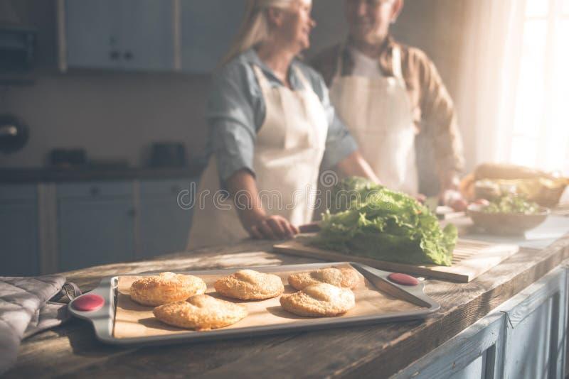 Bollos casados maduros alegres de la hornada de la pareja en sitio del cocinero imagen de archivo libre de regalías