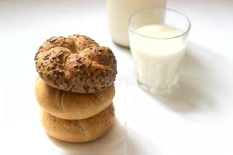 Bollos de Kaiser del trigo y del centeno con las semillas del lino y de sésamo servidas con la leche, desayuno sano fotografía de archivo libre de regalías