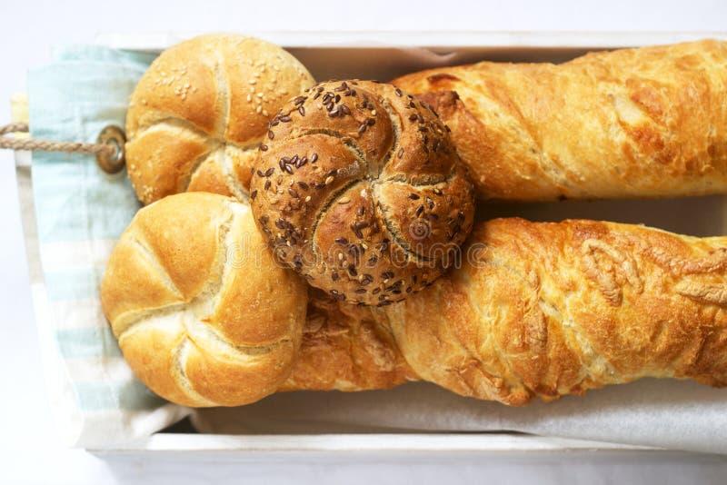 Bollos de la harina del trigo y de centeno de Kaiser con las semillas, los mini baguettes con el jamón y el queso, pan fresco imagen de archivo