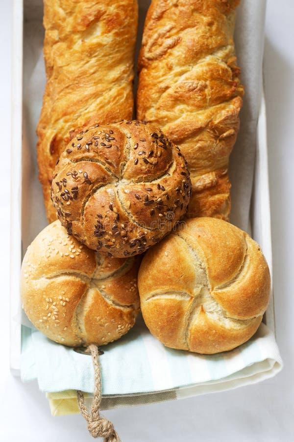 Bollos de la harina del trigo y de centeno de Kaiser con las semillas, los mini baguettes con el jamón y el queso, pan fresco Foc imagen de archivo libre de regalías