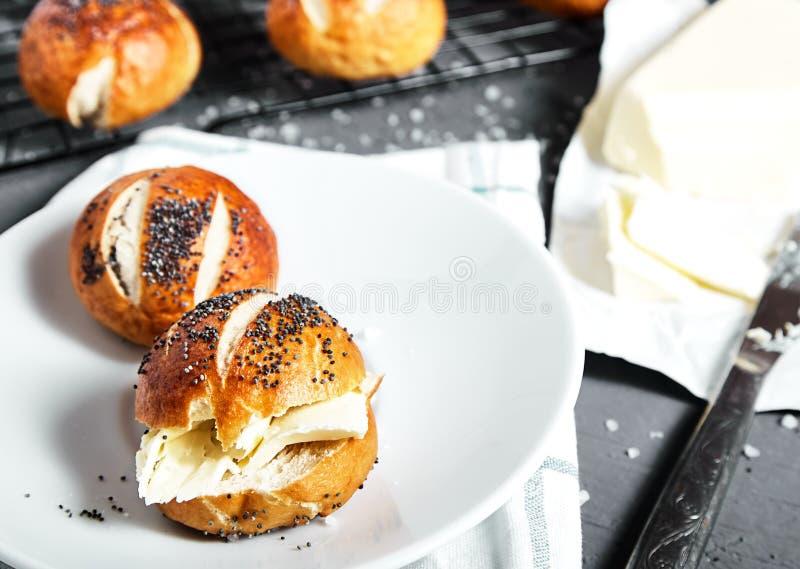 Bollos del pretzel con las semillas y la mantequilla de amapola imagenes de archivo