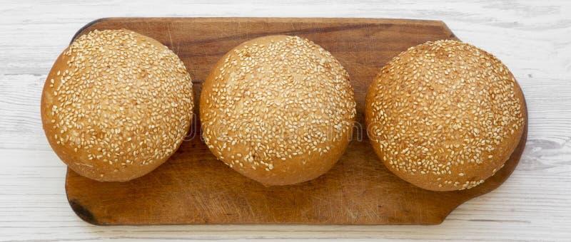 Bollos frescos de la hamburguesa con las semillas de sésamo en el tablero de madera en la superficie de madera blanca, visión de  imagen de archivo