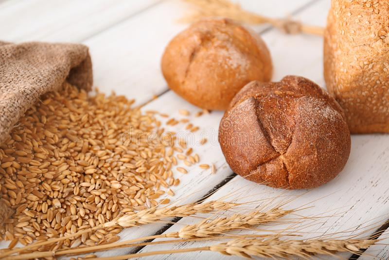 Bollos, granos del trigo y puntos recientemente cocidos en la tabla foto de archivo libre de regalías