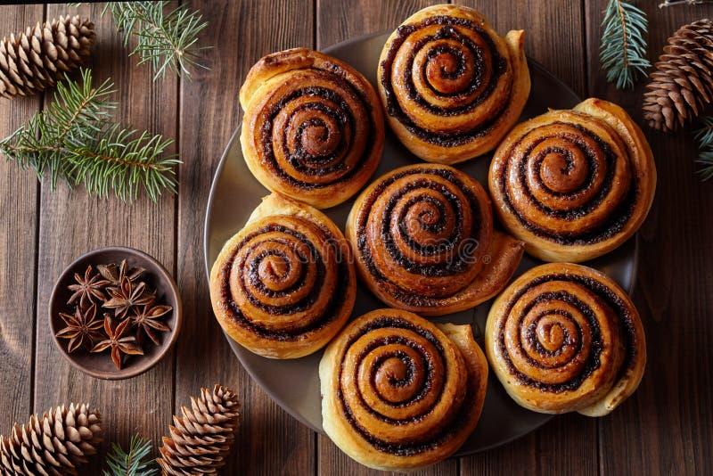 Bollos hechos en casa de los rollos de canela de la hornada de la Navidad con las especias Cocido al horno recientemente Visión s foto de archivo