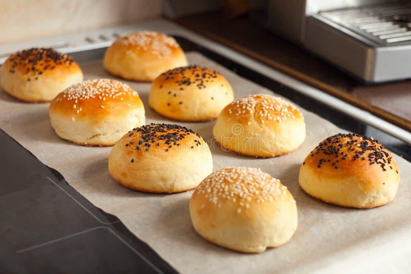 Bollos sabrosos con sésamo Bollos recientemente cocidos al horno Caliente, fresco de los bollos de hamburguesa del horno Bollos d imagenes de archivo