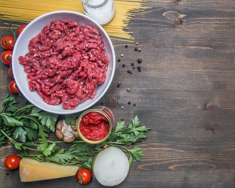 Bolończyka makaronu kulinarny pojęcie, surowy minced mięso, pomidorowa pasta, czereśniowi pomidory, makaron, parmesan, cebule, cz fotografia stock