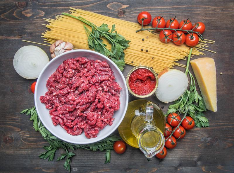 Bolończyka makaronu kulinarny pojęcie, surowy minced mięso, pomidorowa pasta, czereśniowi pomidory, makaron, parmesan, cebule, cz obrazy royalty free