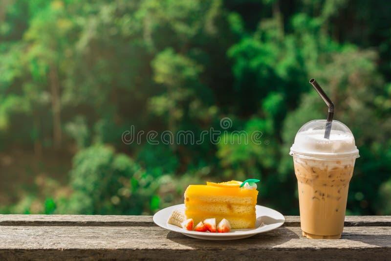Bolo alaranjado delicioso e café congelado do cappuccino na tabela de madeira imagem de stock