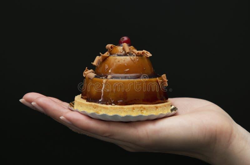 Bolo bonito à moda do caramelo com a baga na palma fotografia de stock