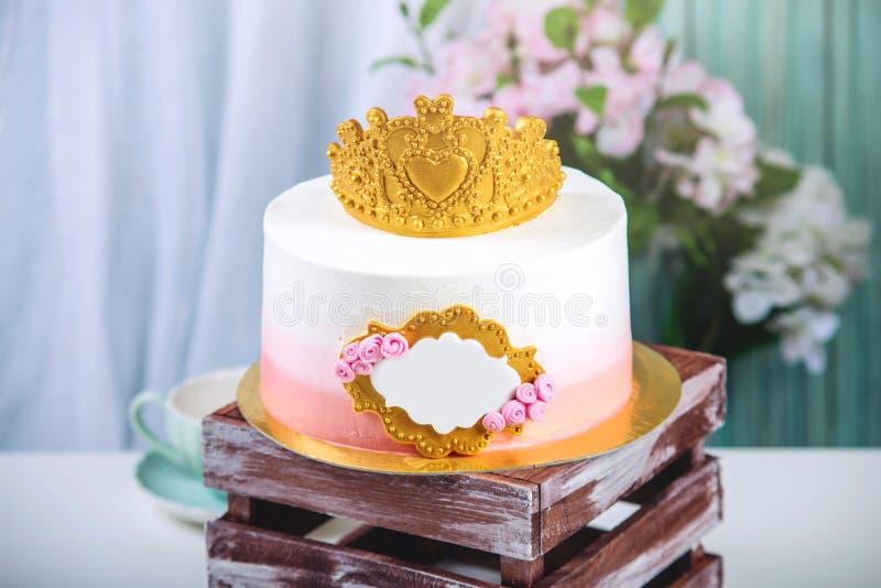 Bolo bonito com uma coroa do ouro na tabela com os copos ao aniversário para uma princesa foto de stock royalty free