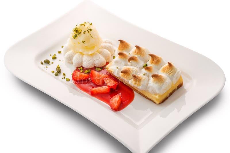 Bolo bonito da baunilha com gelado do limão e molho da morango, pastelaria, sobremesa exclusiva na placa branca fotografia de stock