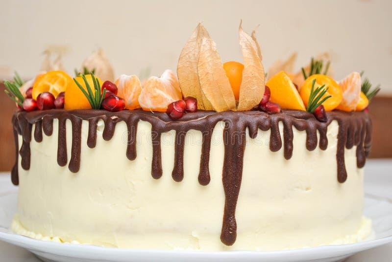 Bolo branco da tangerina inteira com flores dos sizalis e crosta de gelo do chocolate e decoração de Fruts Bolo caseiro da sobrem imagem de stock
