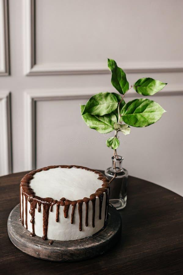 Bolo branco delicioso com chocolate em um suporte de madeira Está em seguida um vaso com uma folha imagens de stock royalty free