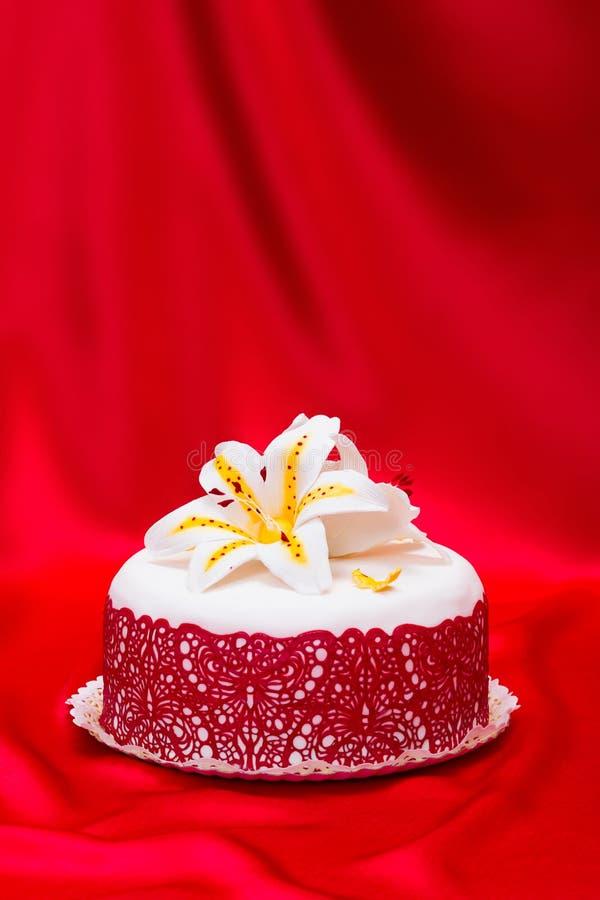 Bolo branco do fundente decorado com laço vermelho e o lírio comestível dos doces imagem de stock