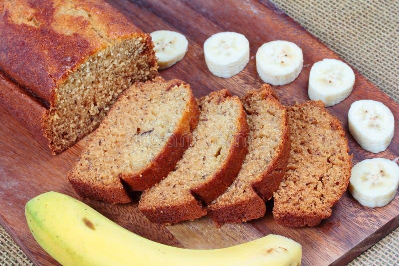 Bolo caseiro da banana com banana cortada e a banana inteira no carniceiro servido foto de stock