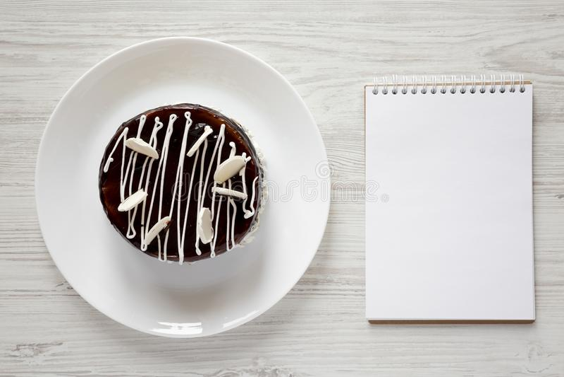 Bolo caseiro da cereja do chocolate e bloco de notas vazio no fundo de madeira branco, vista de cima de Configuração lisa, vista  imagens de stock royalty free