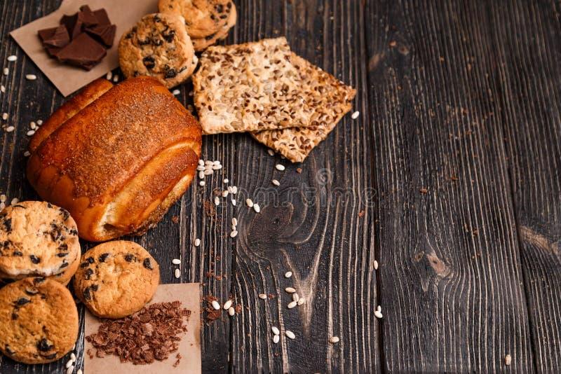 Bolo caseiro e uma variedade de cookies em um fundo de madeira rústico escuro imagens de stock