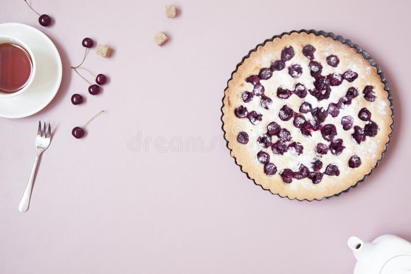 Bolo caseiro inteiro da cereja no fundo cor-de-rosa pastel com bagas e o copo frescos do ch? foto de stock