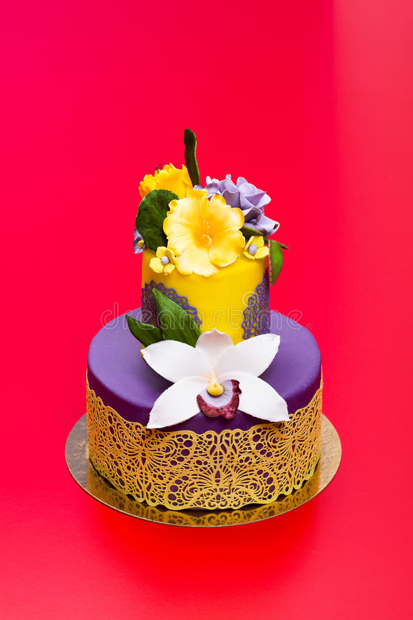 Bolo colorido decorado com flores e laço dos doces fotografia de stock royalty free