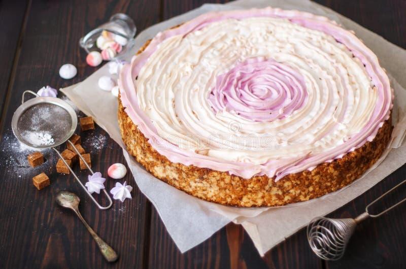 Bolo cor-de-rosa com bagas e merengue na mesa de cozinha imagem de stock royalty free
