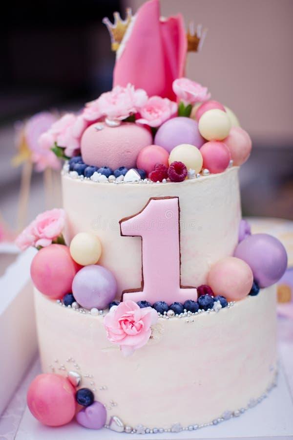 Bolo cor-de-rosa para uma menina no aniversário do bebê de um ano imagem de stock